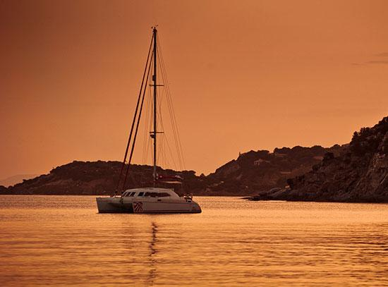 A catamaran anchored in an empty bay under an orange sky that is reflecting in the water and with land visible in the background.