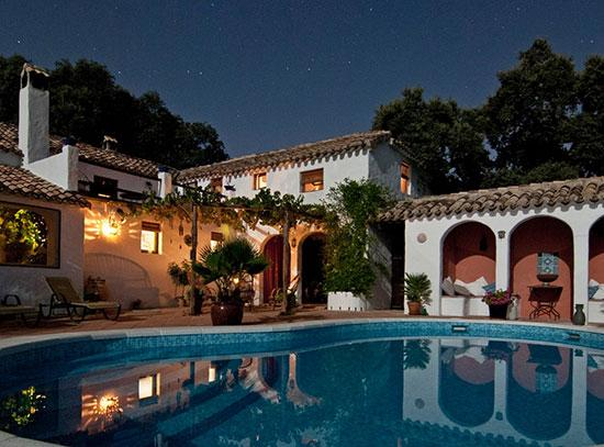 A lavish double story villa at night with a pool in front of it and tall trees behind it.
