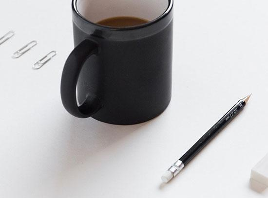 A cup of coffee on a table with paper pins to one side of it and a pencil to the other.