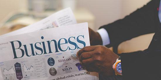 A close up of the arms of an African man in a business suite holding open a business newspaper.