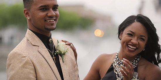 A young luxuriously dressed African couple smiling at the camera.